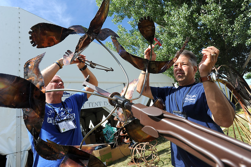 "Chuck Klein, left, and Trey Powers attach pieces to a sculpture titled ""Flying High"" by artist Bill Magaw Thursday, Aug. 11, 2016, in preparation for the upcoming Sculpture in the Park at Benson Park Sculpture Garden in Loveland. (Photo by Jenny Sparks/Loveland Reporter-Herald)"