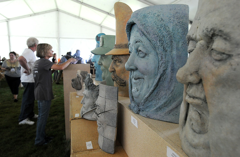 Sculptures of expressive faces by artist Marlys Boddie appear to be watching people as they set up their pieces Thursday, Aug. 11, 2016, in preparation for the upcoming Sculpture in the Park at Benson Park Sculpture Garden in Loveland. Linda Smiley, left, polishes artwork by Dennis E. Conner. (Photo by Jenny Sparks/Loveland Reporter-Herald)