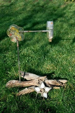 "<h2>Recycle Cycle</h2>cast glass, reclaimed steel and wood  30"" x 26"" x 16"" December, 2001 In this sculpture I wanted to connect seemingly incongruous images (flower, bottle, driftwood, starfish-like lighting fixture) and materials to create an allegory of the interconnectness of all things."