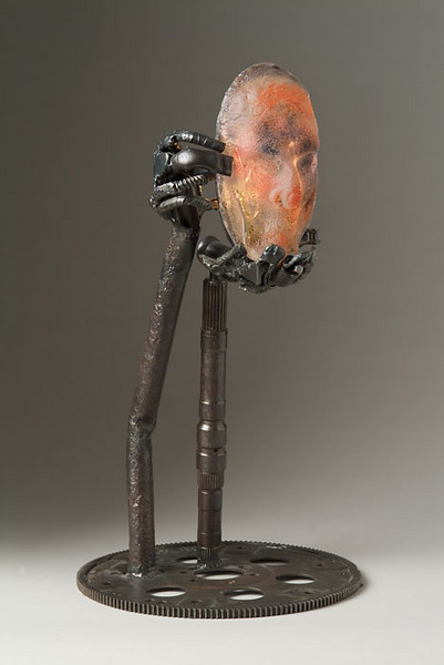 "<h2>Cradled and Revealed</h2>cast glass, reclaimed steel, and electric lighting fixture 27"" x 16"" x 15"" December, 2002 Introspective and eerie, a glass face is held by two steel hands reaching upward.  sculpture © Bill Hess"