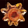 "<h2>Sunshine</h2>cast glass with steel mounting bracket 15"" x 15"" x 2"" July, 2002 The sun has symbolism of unity and wholeness- the secondary ring gear inclusion ironically seems to emphasize this."