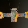 "<h2>Crossing the Ages</h2>cast glass 26"" x 10"" x 2"" April, 2003 Discarded consumer items are integrated into this piece to create a spiritually inspired piece.  sculpture © Bill Hess"