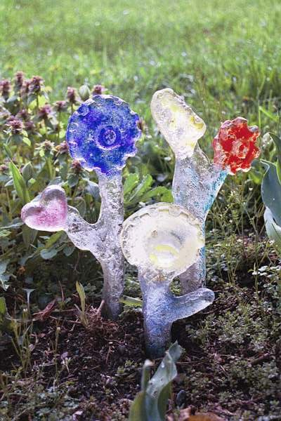 "<h2>Flowers</h2>cast glass varying sizes  8-14"" high November, 2000 This sand-cast ""flower"" was formed from natural and human-made discarded parts. This is a rugged piece of glass art that can be firmly planted and left in the ground year `round to liven up your home.  I enjoy transforming discarded materials into a provocative visual statement that allows us to examine today's artifacts from another perspective."