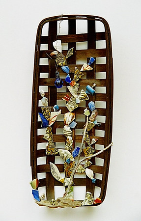 """Thought #1"" 2005, mixed-media creation composed of  a wooden basket, pottery shards, seashells, glass bottle stopper, wire, piece of driftwood and a branch"