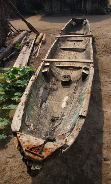 Dugout log canoes like this one next to a house in Digirdup are still commonly used.  Most now have a small outboard motor.