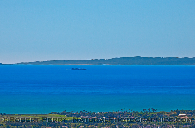Container cargo vessel northbound in the Santa Barbara Channel with Santa Rosa Island in the back.