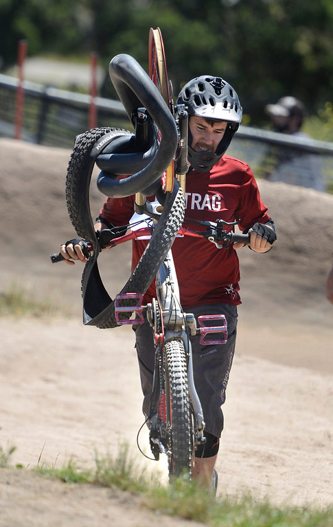 . Dual Slalom racer Trever Meier of Sacramento rolls his bike of the course after damaging his front tire in a crash during the Sea Otter Classic Cycling Festival at Laguna Seca Raceway in Monterey on Friday April 21, 2017. (David Royal - Monterey Herald)