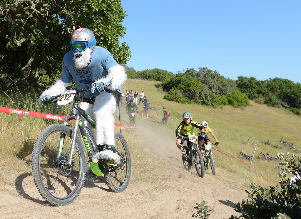. Yuri Haustwald leads a group of riders around a corner while wearing a yeti costume during the Haibike electric mountain bike race (e-MTB) race at Sea Otter Classic Cycling Festival at Laguna Seca Raceway in Monterey on Friday April 21, 2017. Haustwald was riding one of Haibike\'s electric bikes in the industry division.(David Royal - Monterey Herald)
