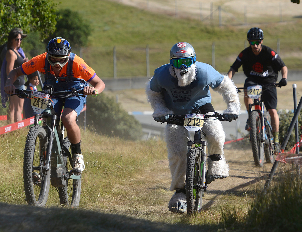 . Yuri Haustwald wears a yeti costume as he passes Tyler Pattullo, left, during the Haibike electric mountain bike race (e-MTB) race at Sea Otter Classic Cycling Festival at Laguna Seca Raceway in Monterey on Friday April 21, 2017. Haustwald was riding one of Haibike\'s electric bikes in the industry division.(David Royal - Monterey Herald)