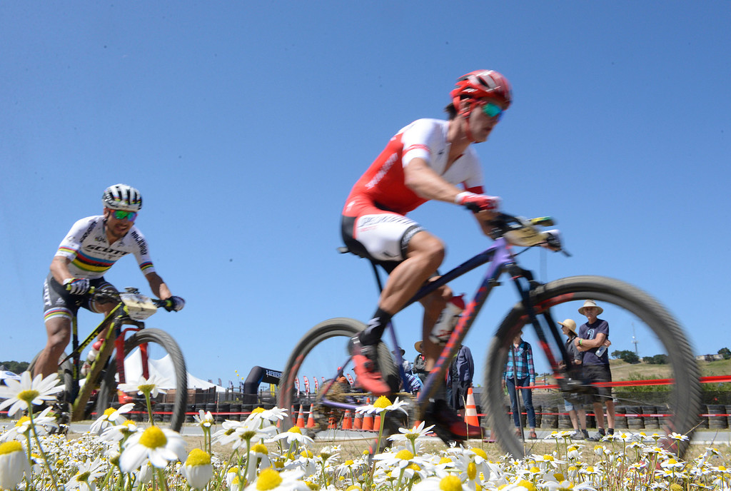 . Sam Gaze, right, of New Zeland leads reigning World Champion and Olympic gold medalist Nino Schurter of Switzerland past a patch of wildflowers during the Mens Pro Short Track race at the Sea Otter Classic Cycling Festival at Laguna Seca Raceway in Monterey on Friday April 21, 2017. Gaze won the race, Schurter took second. (David Royal - Monterey Herald)