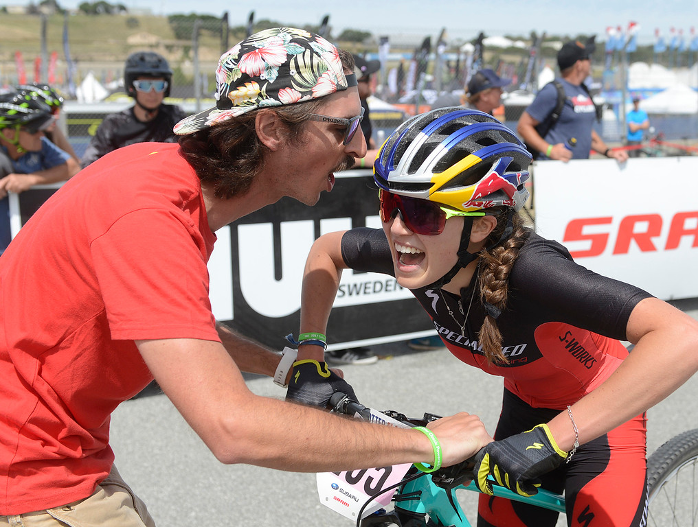 . Brad Copeland Specialized Bicycles racing team mechanic greets Kate Courtney of Morgan Hill after her win during the Women\'s Pro Cross Country Mountain Bike race during the Sea Otter Classic Cycling Festival at Laguna Seca Raceway in Monterey on Saturday April 22, 2017. (David Royal - Monterey Herald)