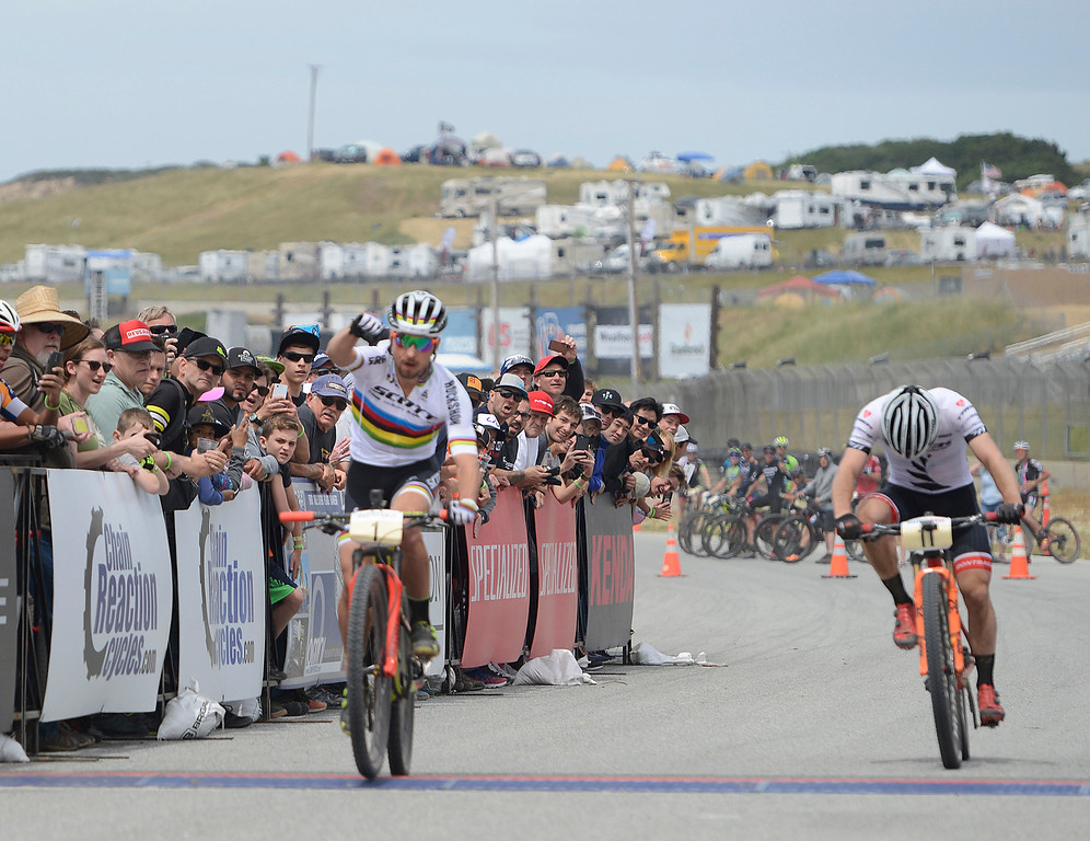 . Swiss rider Nino Schurter throws his fist up as he crosses the finish line ahead of Anton Cooper of New Zealand during the Men\'s Pro Cross Country Mountain Bike race during the Sea Otter Classic Cycling Festival at Laguna Seca Raceway in Monterey on Saturday April 22, 2017. (David Royal - Monterey Herald)