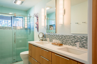 Master bathroom with floating double vanity and glass tile shower.