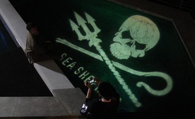 "Guests pose over the Sea Shepherd Light Hologram in the pool.  Sea Shepherd launch party for the ""Operation No Compromise"" Antarctic Whale Defense Campaign and the Gojira Interceptor Vessel unveiling in Los Angeles, CA. on October 23, 2010"