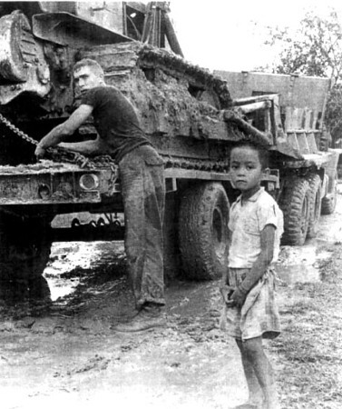 EON3 Rees and Friend at the orphanage approach road at Thu Duc, Gia Dinh Province...28 Sept 67 to 06 June 68<br /> Photo:Seabee Team Deployment Completion Report