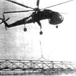 A flying crane lifts a pre-assembled 27 meter Eiffel bridge into position for Team 7108 in the Coconut Grove region, Go Cong Province. The bridge and 8 kilometers of new road opened a large area to re-settlement.<br /> Photo: Seabee Team Deployment Completion Report