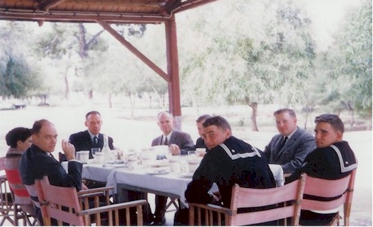 Lunch on the way to Corinth, Greece April 1961.  Left to right around the table: CWO Goodson, lady tour guide, Captain Colbert, CDR Scoggins, senior supply officer, CWO Downs (mostly hidden from view), an unidentified supply officer, George Hanson (Captain Colbert's driver) and, foreground center, duty driver Charles M. Swett, BM2, 1958-1960.  Can anyone help with ID's?