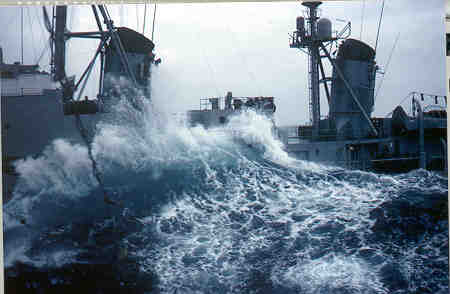 USS Newman K. Perry  DD-883 takes a wave.  One crewman injured and taken thru hatchway for medical help.