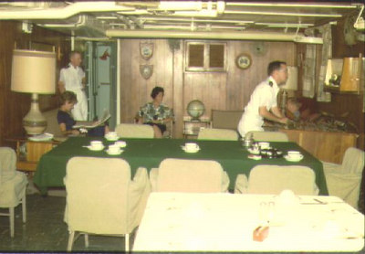In the Altair wardroom with their wives are LT Joe McClain (left) and LTJG Steve Woody (right) 1963.