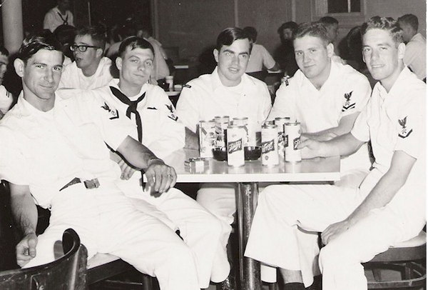 Ah, liberty!  Jerry Pelton  (L), Jim DeSantis, SK3 2nd from left, Jim Malay center,  and Thomas A. Head SK3 far right are relaxing with shipmates.  Gooch Gladwell is the kid in the glasses on the top left.  Does anyone recognize the other shipmate?