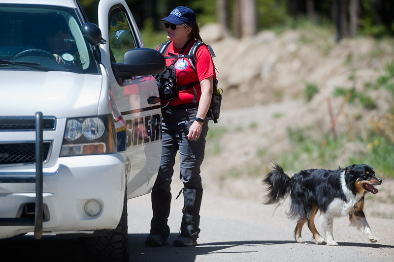 "Terrie Kirkpatrick, with Front Range Rescue Dogs, talks with a Boulder County sheriff's deputy at Eldora Mountain Resort with Tia, an English shepherd, one of four dogs involved in the search for human remains at the ski resort on Thursday. <br /> More photos:  <a href=""http://www.dailycamera.com"">http://www.dailycamera.com</a><br /> Autumn Parry/Staff Photographer<br /> June 2, 2016"