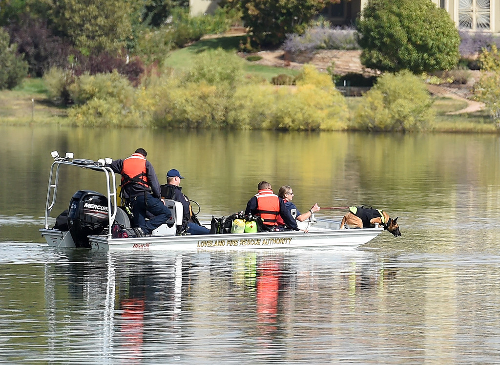 . Saker, a Larimer County Search and Rescue live-find K9, leans off of the boat sniffing as his handler, Denise Alvord, along with other members of the team and Loveland Fire Rescue Authority Special Operations Team dive members search for a missing kayaker Monday, Oct. 1, 2018, at Buckingham Lake in west Loveland.  (Photo by Jenny Sparks/Loveland Reporter-Herald)