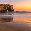 Golden light illuminates Natural Bridges rock formation and the beach.