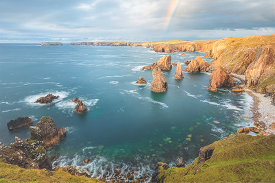 Golden hour light and rainbow over dramatic rocky landscape seascape of Mangersta Sea Stacks on the coast of the Isle of Lewis in the Outer Hebrides of Scotland, UK.