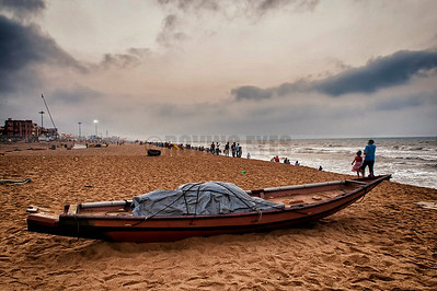 B15:A fishing boat lies all packed up,it's use over for the morning,as tourists crowd the beach in Puri,Odissa