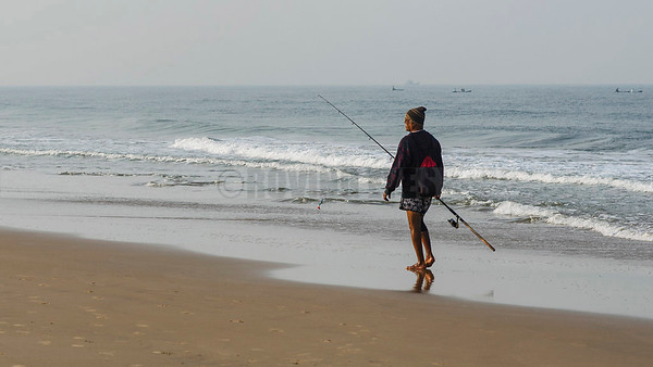 B8:The angler walks the beach,looking for a suitable spot to cast his rod in Calangute,Goa