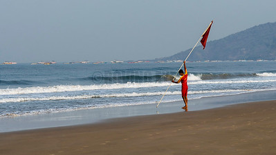 B9:The lifeguard sets up a marker flag early in the morning before tourists arrive in Calangute,Goa