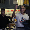 Joe Terry runs the holiday auction for the Time Warp Vintage Motorcycle Club as Geoffrey and George watch. Roger peeks our from behind the apparel rack.