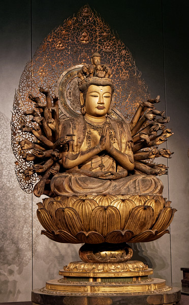 Seated Thousand-armed Kannon Bosatsu (Sahasrabhuja). Wood with gold pigment, cut gold leaf, and inlaid crystal eyes. Nanbokucho period, 14th century. The compassionate deity Sahasrabhuja uses his thousand arms to save those in need.