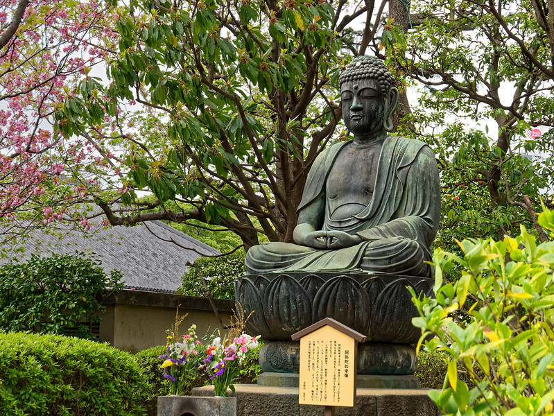In a side garden, this Buddha figure sits in meditation.