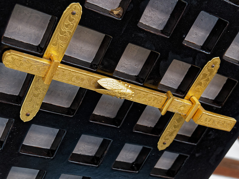 A golden cicada graces a latch used to hold a window-covering panel open.