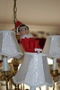 11-29-2010 DAY 4 - ELF ON DINING ROOM CHANDELIER When Santa allowed FELF, our elf, to return on the fourth day, he moved to a spy perch on the dining room chandelier.  Cameron found him there while he got ready for school.