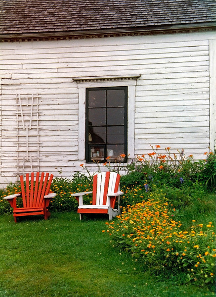 Chairs New Brunswick Canada, 1981<br /> <br /> A vintage photograph of colorful chairs and home in a rural area of New Brunswick Canada.