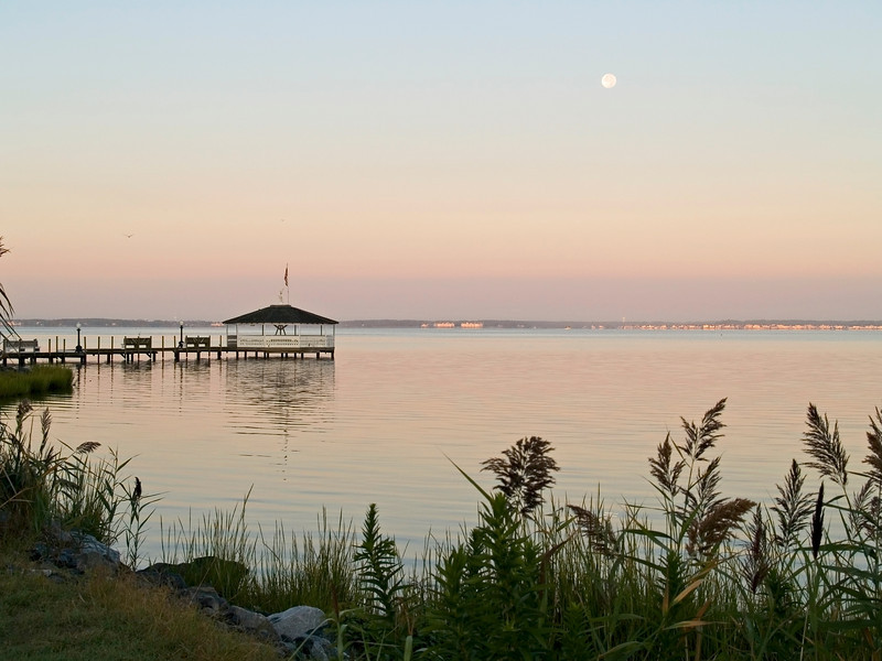 The moon over the bay at sunrise in Ocean City Maryland.