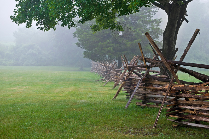 """Battlefield Fence""  A Wooden fence along the open field in Monmouth Battlefield State Park on a foggy Summer morning."