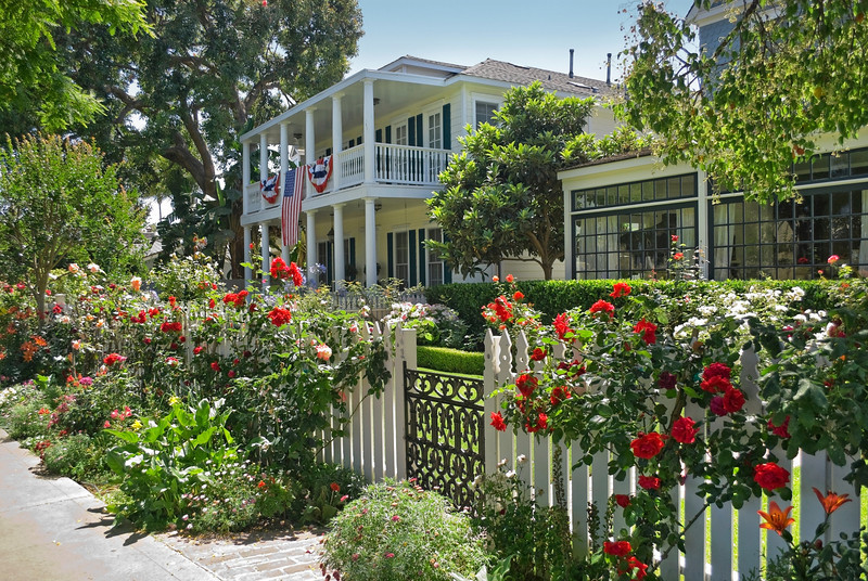 A beautiful garden and white picket fence surrounds this Coronado California home.