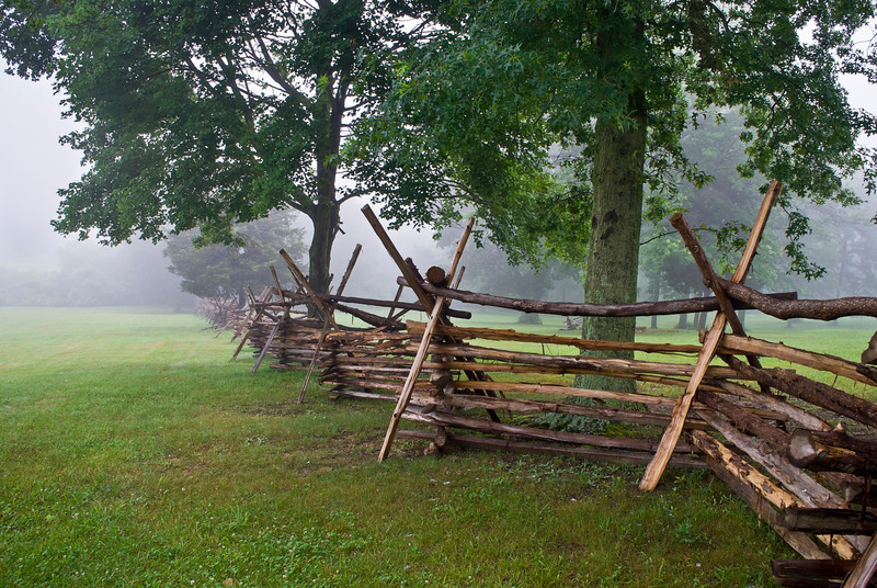 """Monmouth Battlefield""  A Wooden fence along the open field in Monmouth Battlefield State Park on a foggy Summer morning."