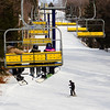Skier & Snowboarders going up a mountain in yellow chairlift
