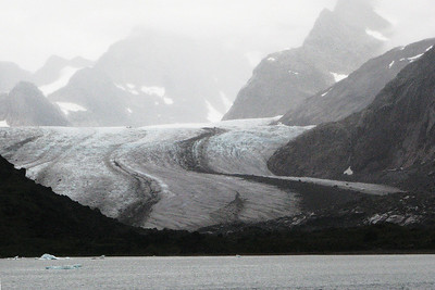 Glaciers join as rivers do to form larger glaciers.  Greenland glacier with medial moraine showing where two glaciers came together.  Terminal moraine shows pushed rock and boulders in front.