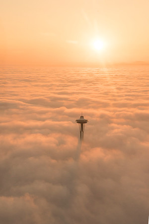 Space needle at sunset above a blanket of clouds