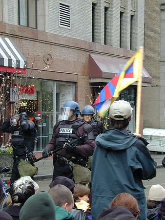 A man waves the Tibetan flags as a cop dons a gas mask.