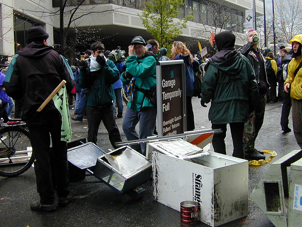 An early sign of vandalism; newspaper dispensers and trash cans used as a traffic barricade.