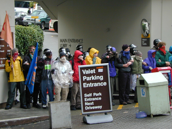 A line of protesters flanked by a line of riot police at the valet parking entrance of the Sheraton.