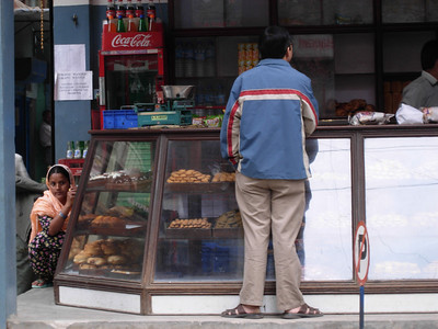 While in Nepal, I was photography the case of pastires across the street. I didn't see the squatting woman until later.  Photographer's Name: Anita Elder