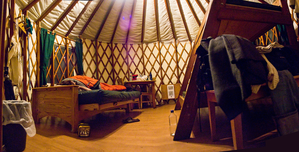 <b>INSIDE THE YURT:</b>  The yurts were quite luxurious as far as camping is concerned.  Here is a clumsy photo-stitch that I created showing the inside of the yurt. None of my lenses could capture the whole interior, so I took several shots and pieced them together.  In this shot, Ruth relaxes on a futon folded into its bed configuration and there is a bunk bed on the right side of the room.  The yurt has electricity and a heater too... nice!