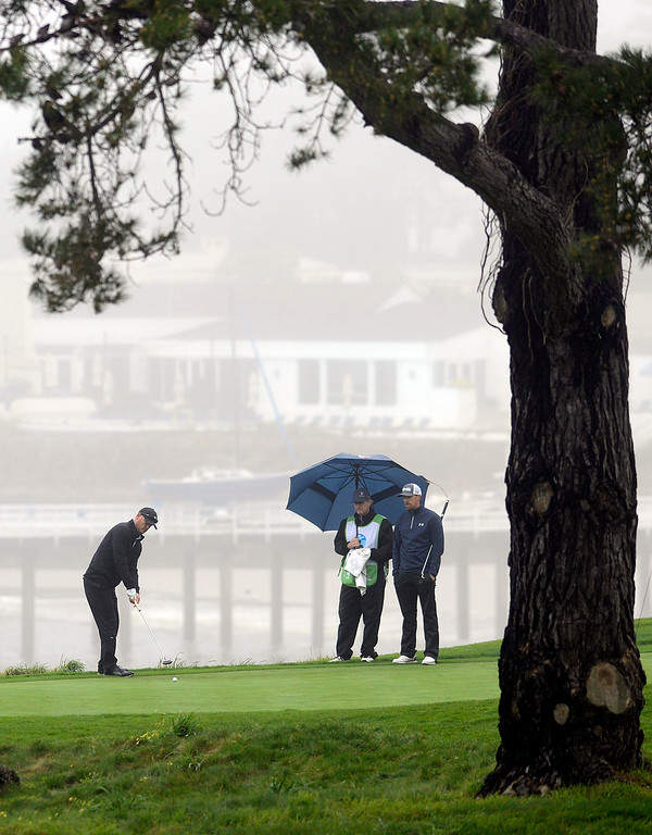 . Troy Merritt putts on the fifth green as Hunter Mahan watches as rain rolls in at Pebble Beach Golf Links during the second round of the AT&T Pebble Beach Pro-AM in Pebble Beach on Friday February 10, 2017. (David Royal - Monterey Herald)
